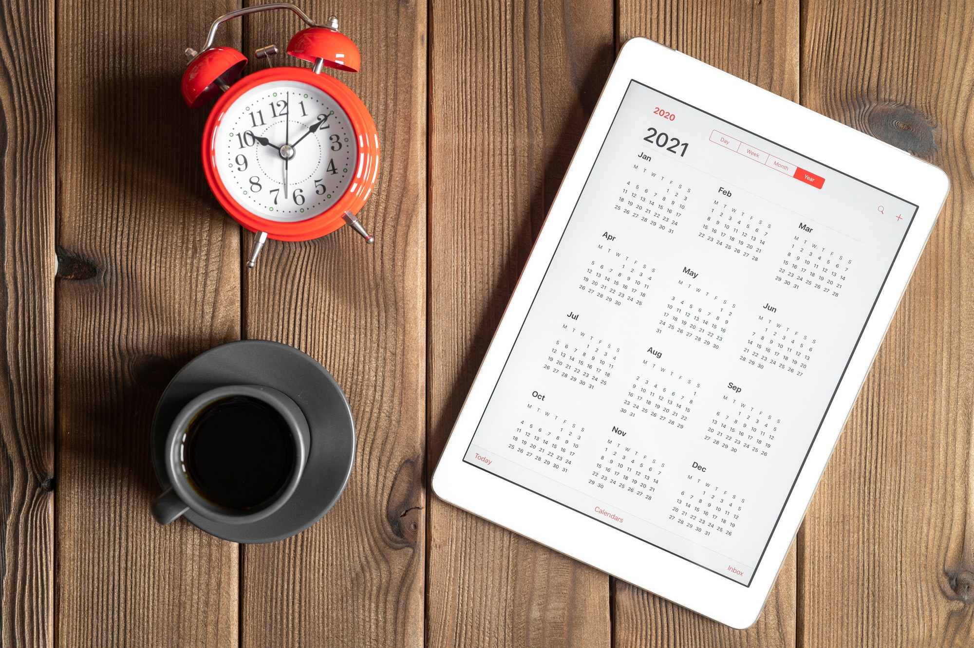 tablet with calendar for 2021, a cup of coffee and a red alarm clock on a wooden background flat lay