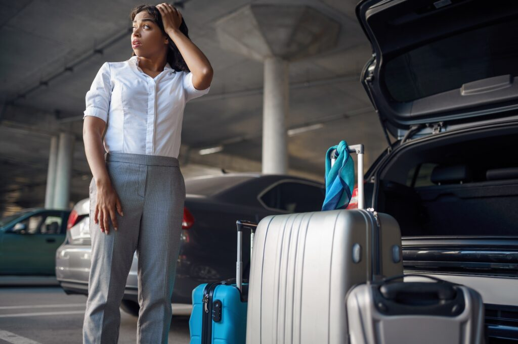 Young woman with suitcases in a panic, car parking